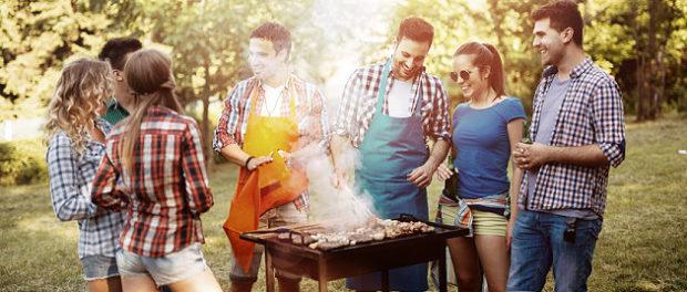 Junge Leute stehen um einen Grill